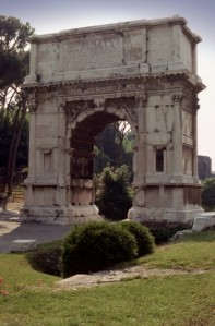 The Arch of Titus from outside the Forum, Rome, Italy.  Located at the highest point of the Via Sacra which leads to the Roman Forum, this triumphal arch, with only one passageway, commemorates Titus' conquest of Judea which ended the Jewish Wars (66-70). Engaged fluted columns frame the passageway.